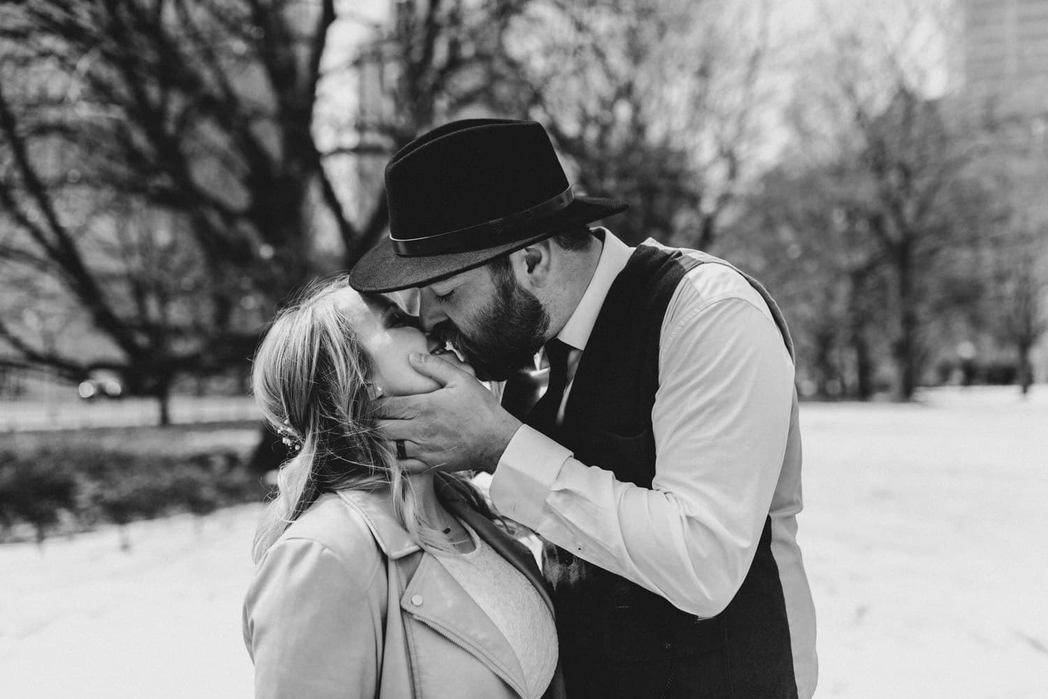 black and white portrait of bride and groom kissing