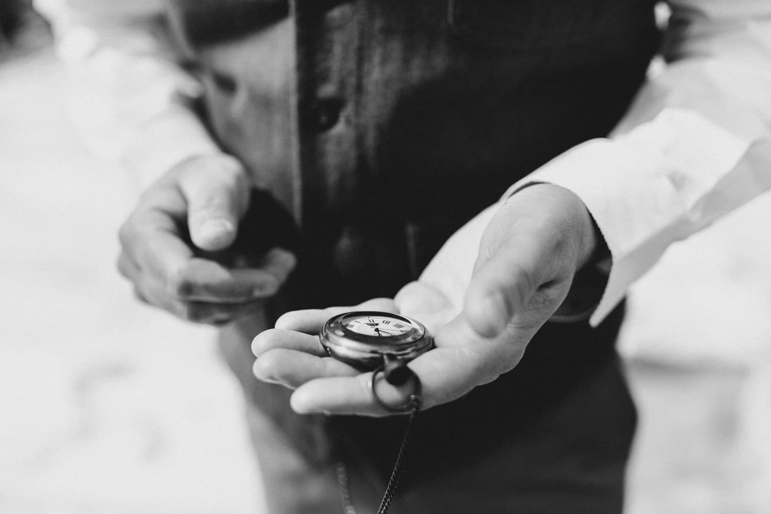 groom checks vintage pocket watch