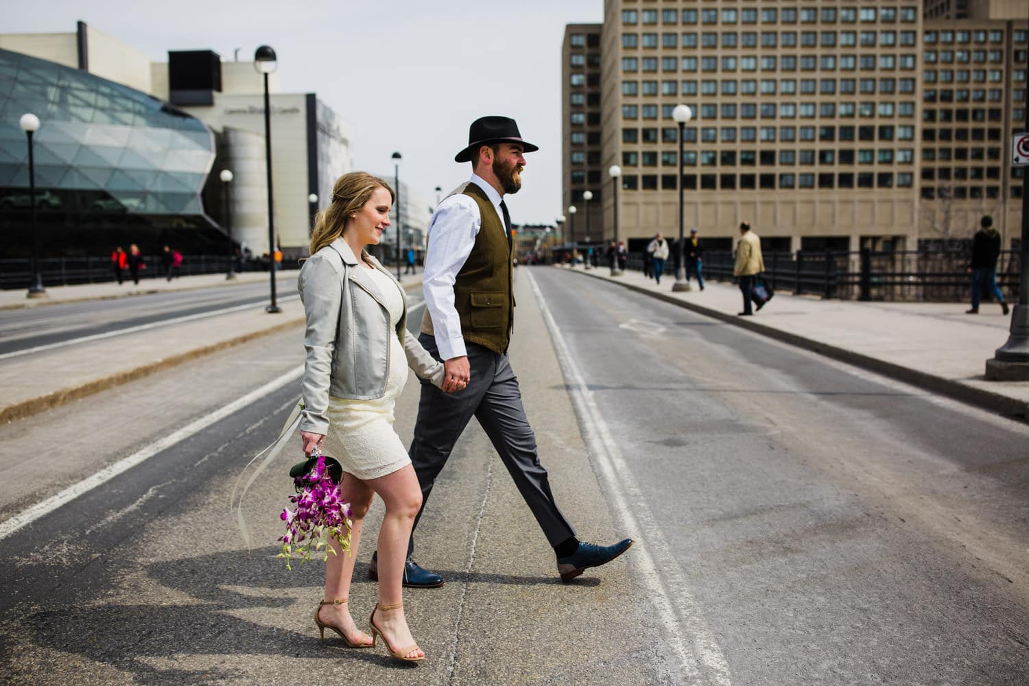 bride and groom cross the street in ottawa