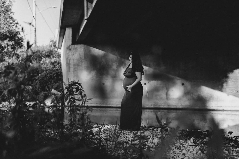 pregnant woman stands under bridge