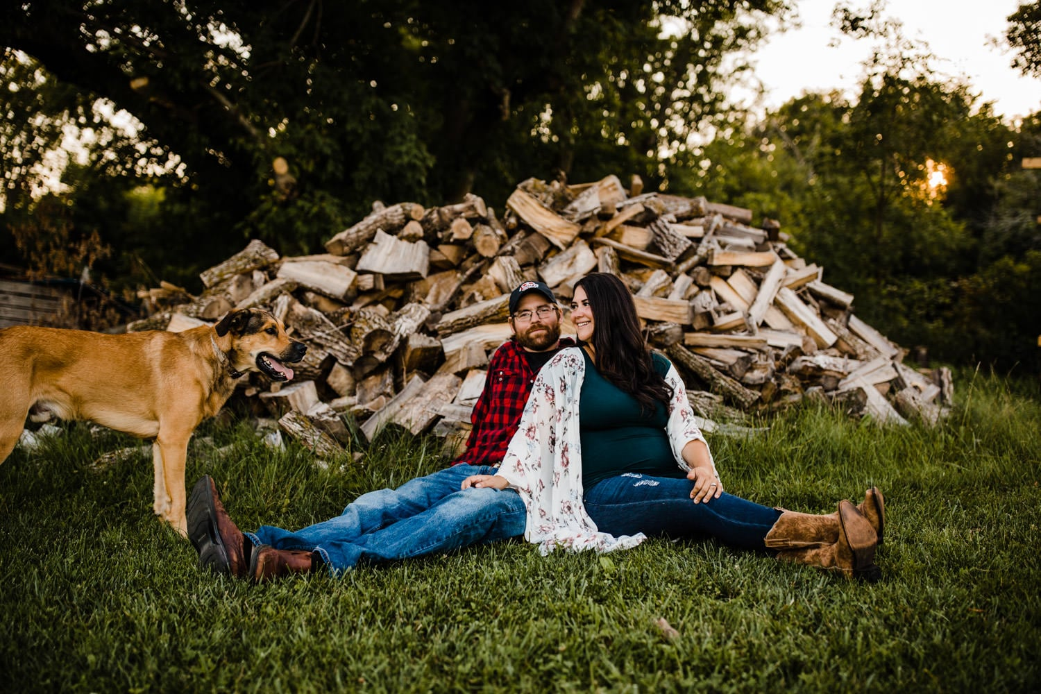 expectant couple sit in front of wood pile with their dog - ottawa maternity photographer