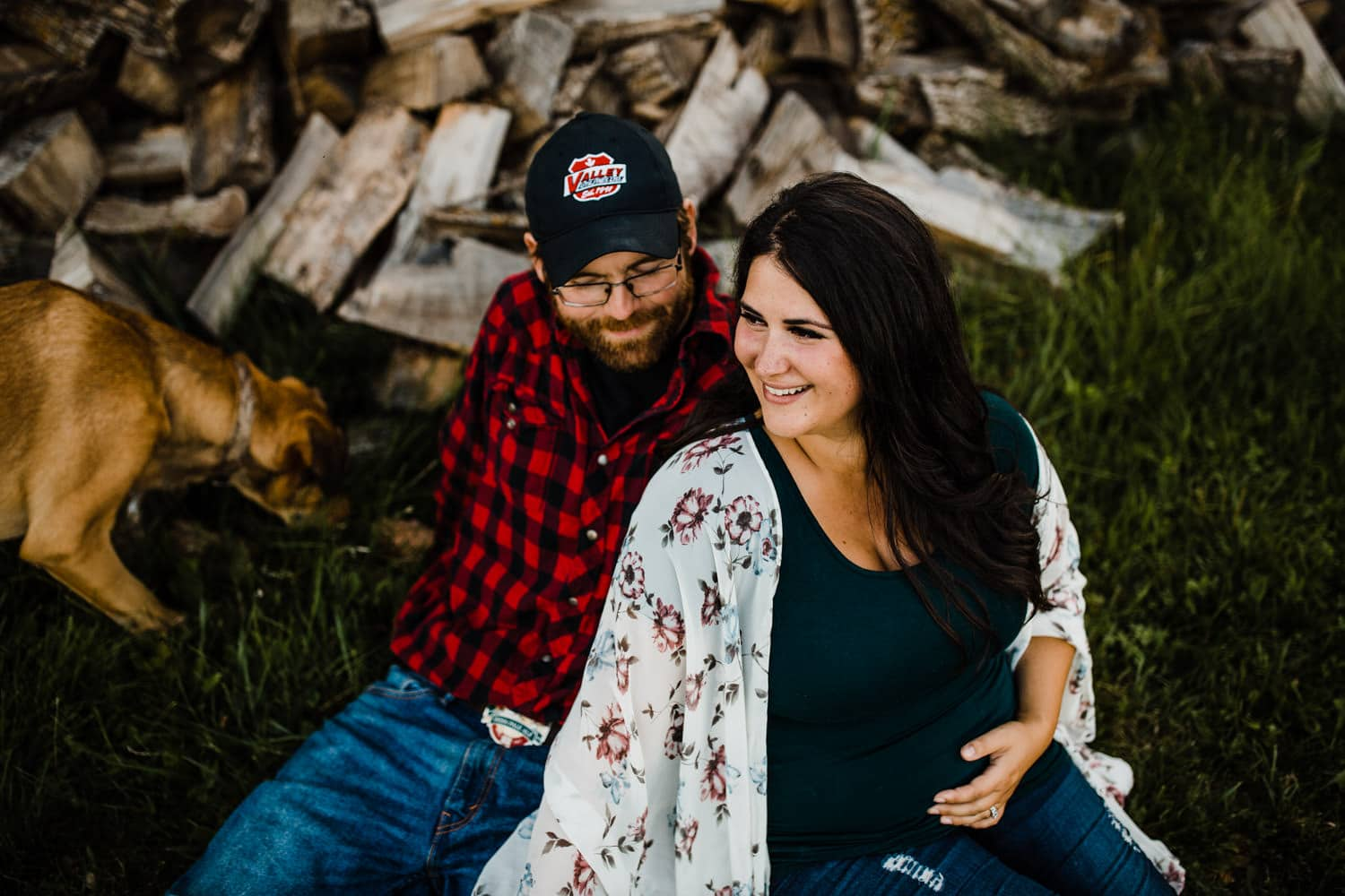 expectant couple sit in front of wood pile - lifestyle maternity photographer