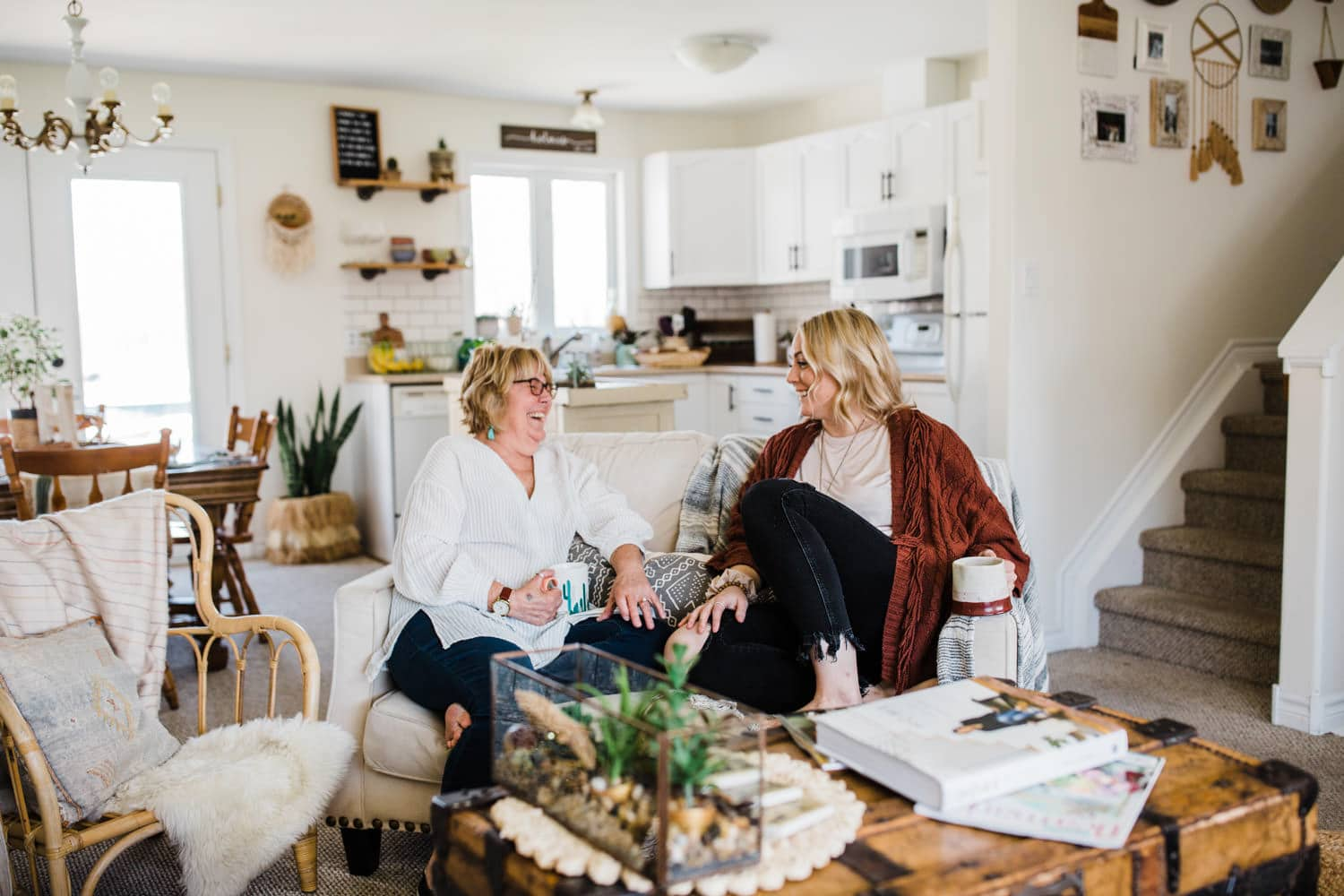 mother and daughter laugh together in living room - small business brand photography