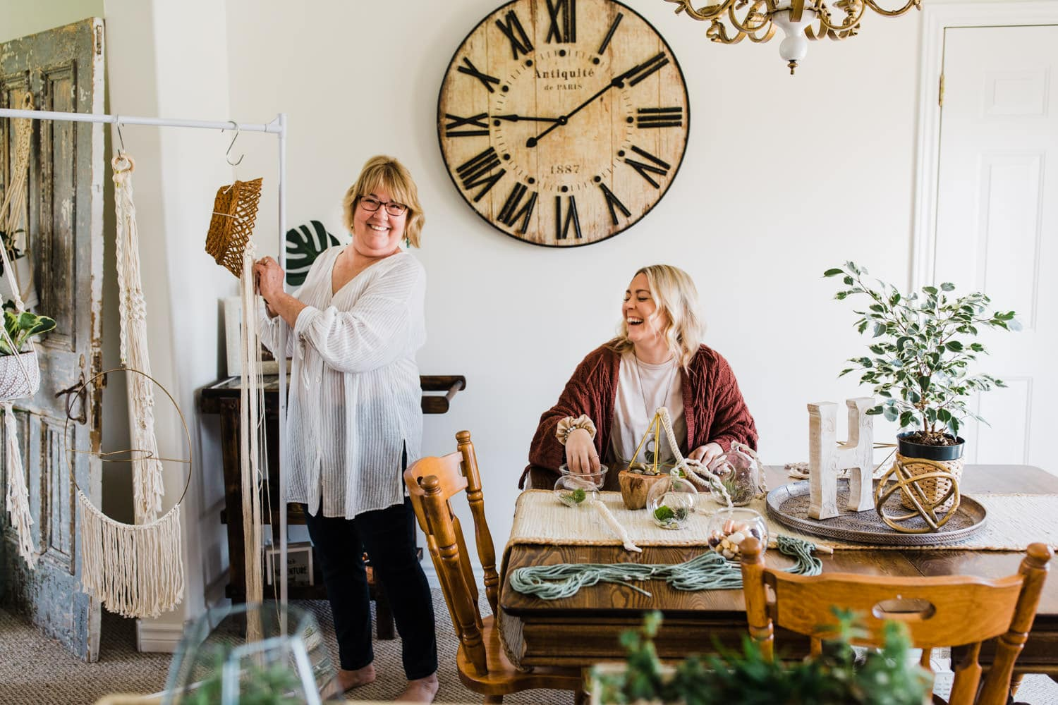 mother and daughter laugh together as they work on their small business products in dining room - brand photography ottawa