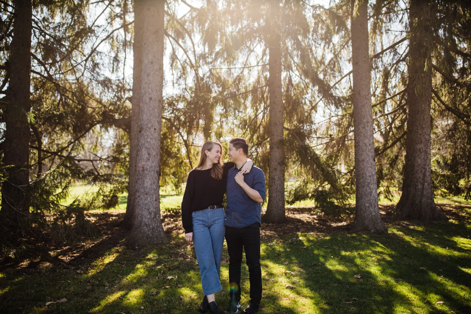 engaged couple pose for photos as sun peeks through trees behind them