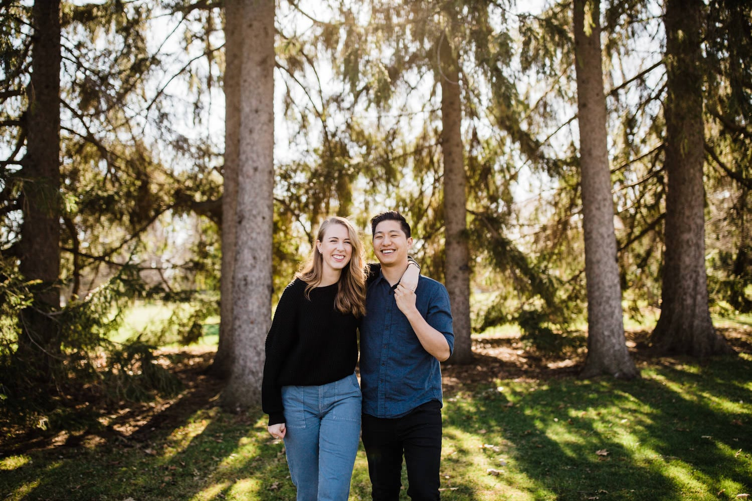 couple laugh together as sun shines through trees behind them - ottawa experimental farm engagement