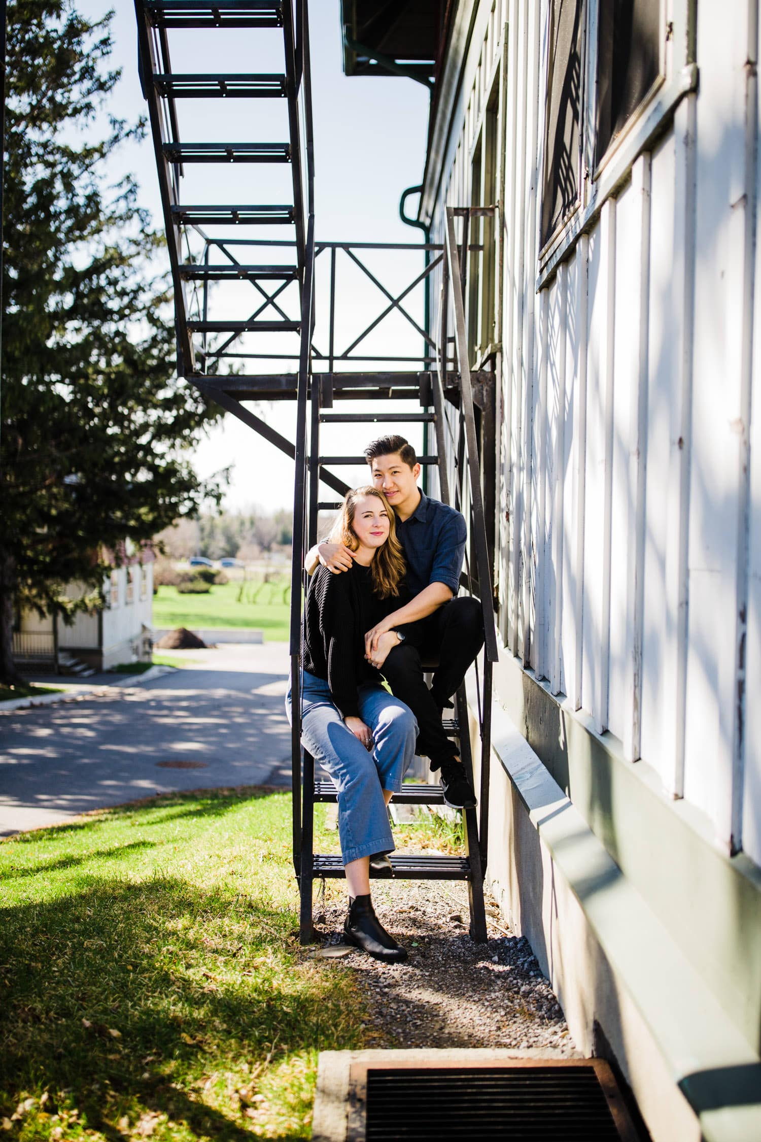 couple sit on fire escape stairs together - ottawa engagement photographer