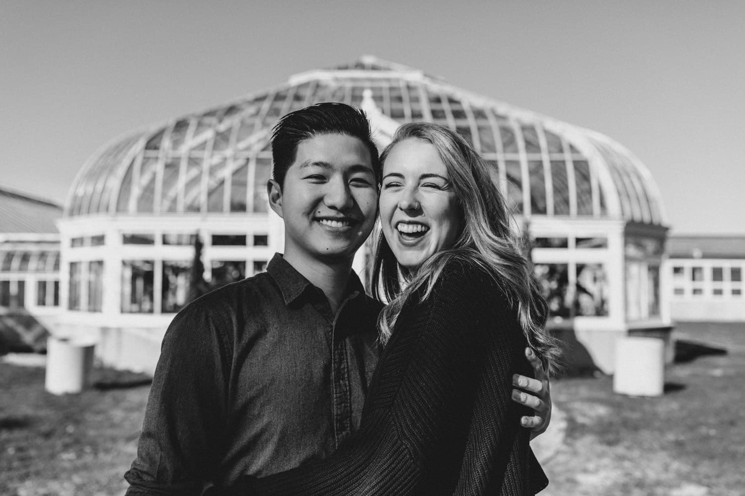 couple laugh together in front of tropical greenhouse - ottawa engagement photographer