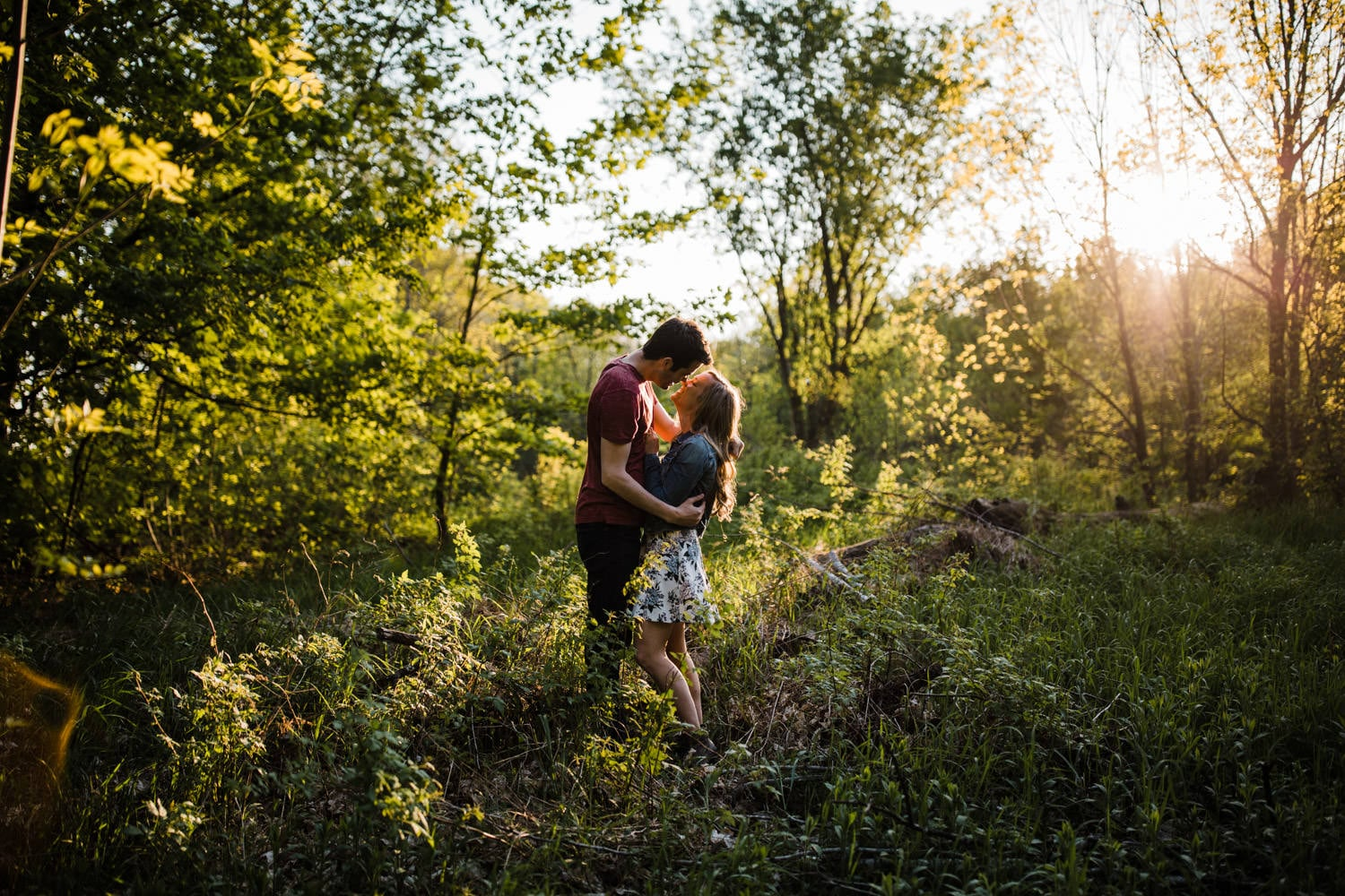 Couple stand together in tall grass as sun sets behind them
