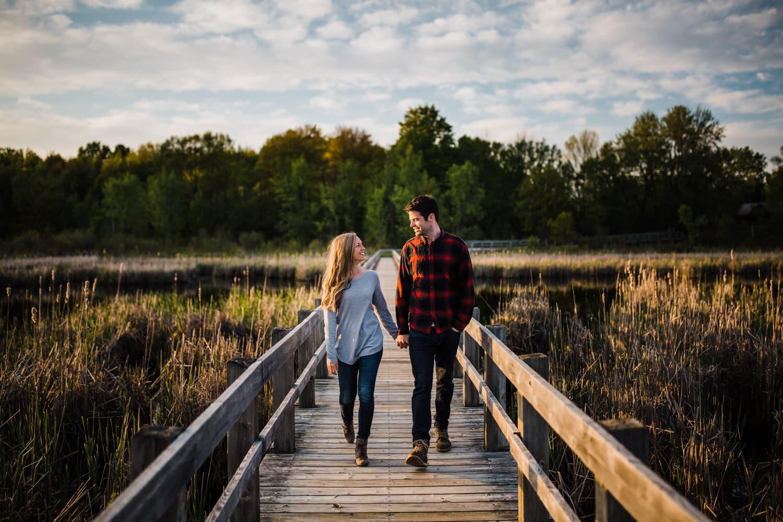Couple walk together on boardwalk - mer bleue engagement