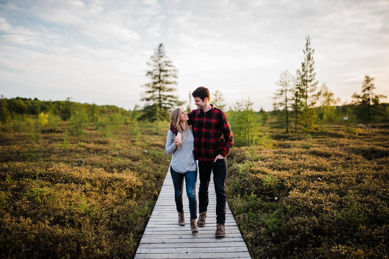 Couple walk together through bog area - mer bleue engagement