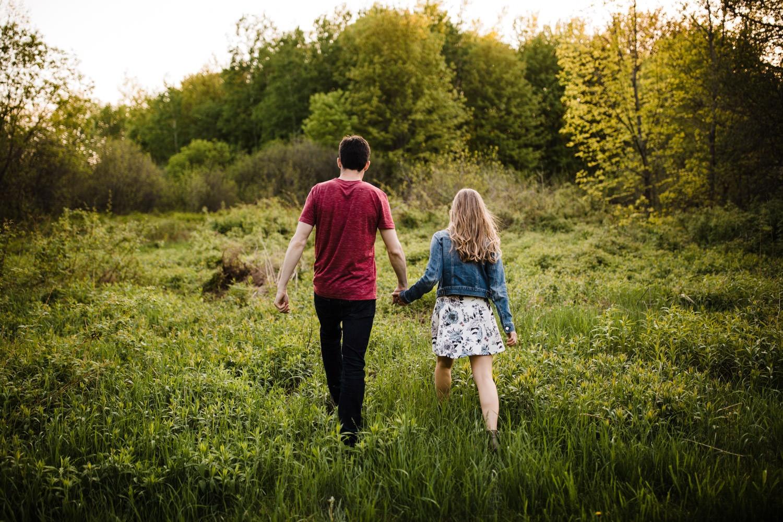 Couple walk hand-in-hand through tall grass - Mer Bleue Engagement