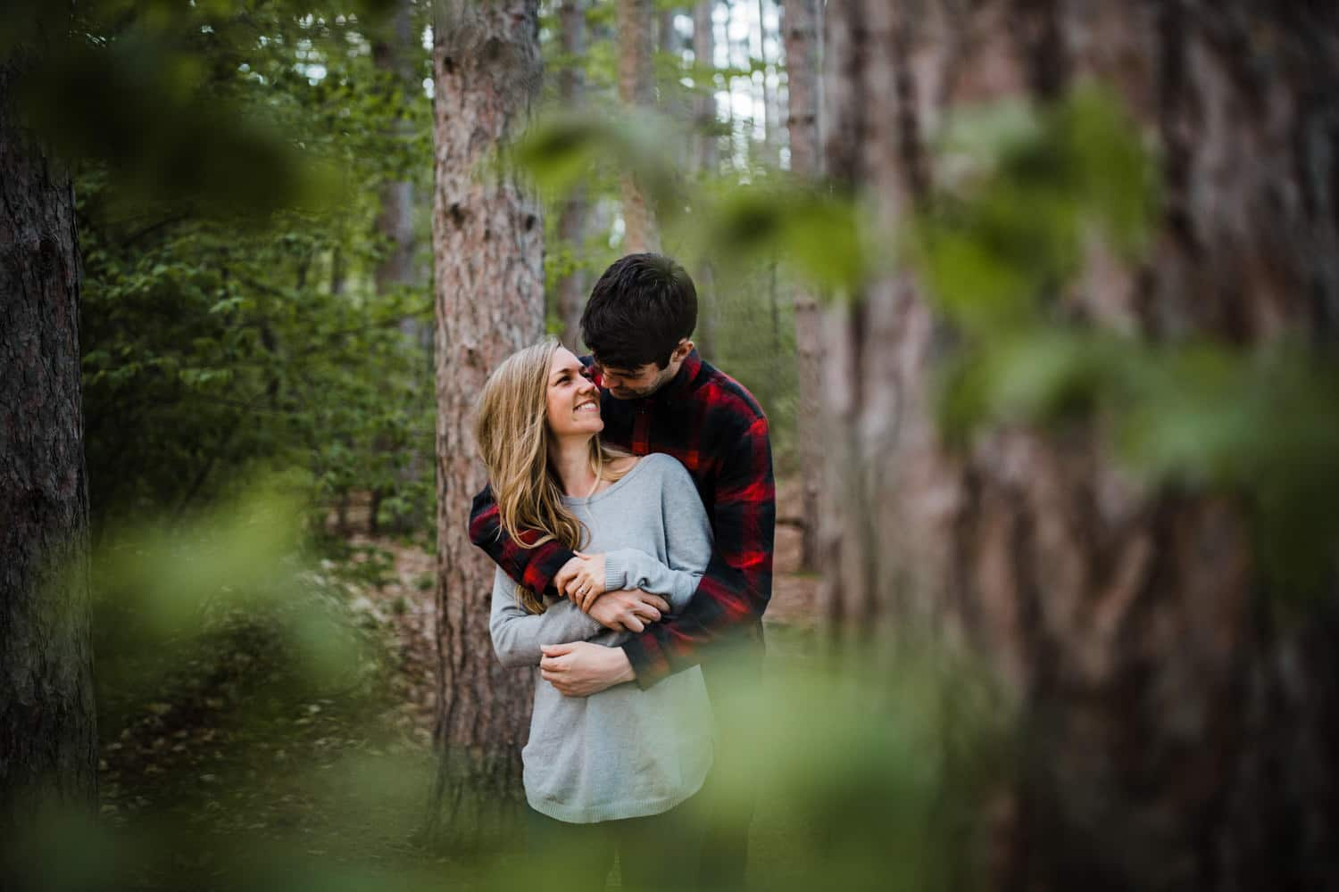 Couple stand together in forest - mer bleue engagement