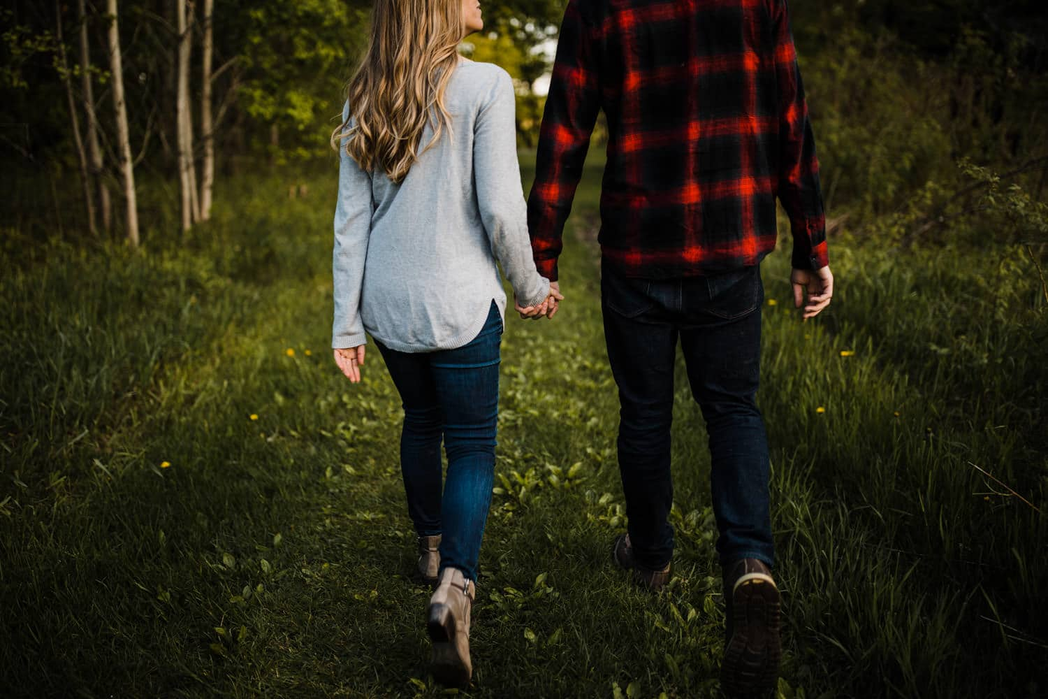 Couple walk hand in hand outdoors together