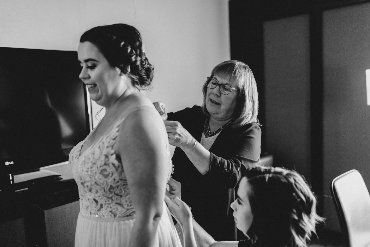 brides mom and sister help her into dress
