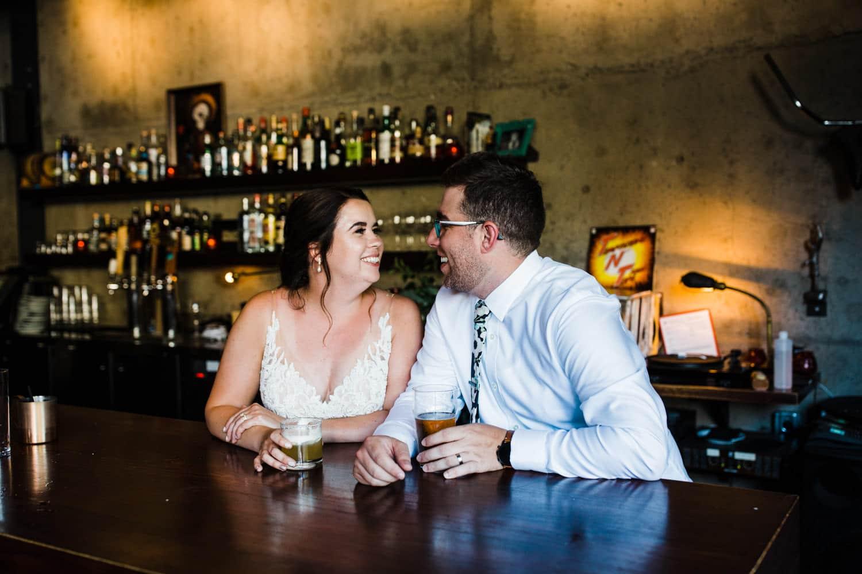 bride and groom sit at the el camino bar - downtown ottawa wedding