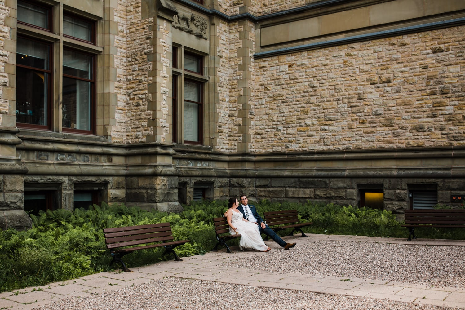 bride and groom sit on bench together - downtown ottawa feeling
