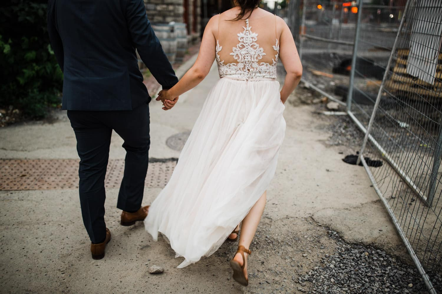bride and groom walk through construction as wind blows - downtown ottawa wedding