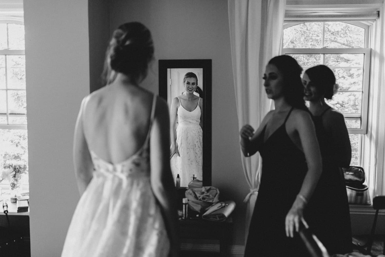 bride looks in mirror at her dress - ottawa backyard wedding