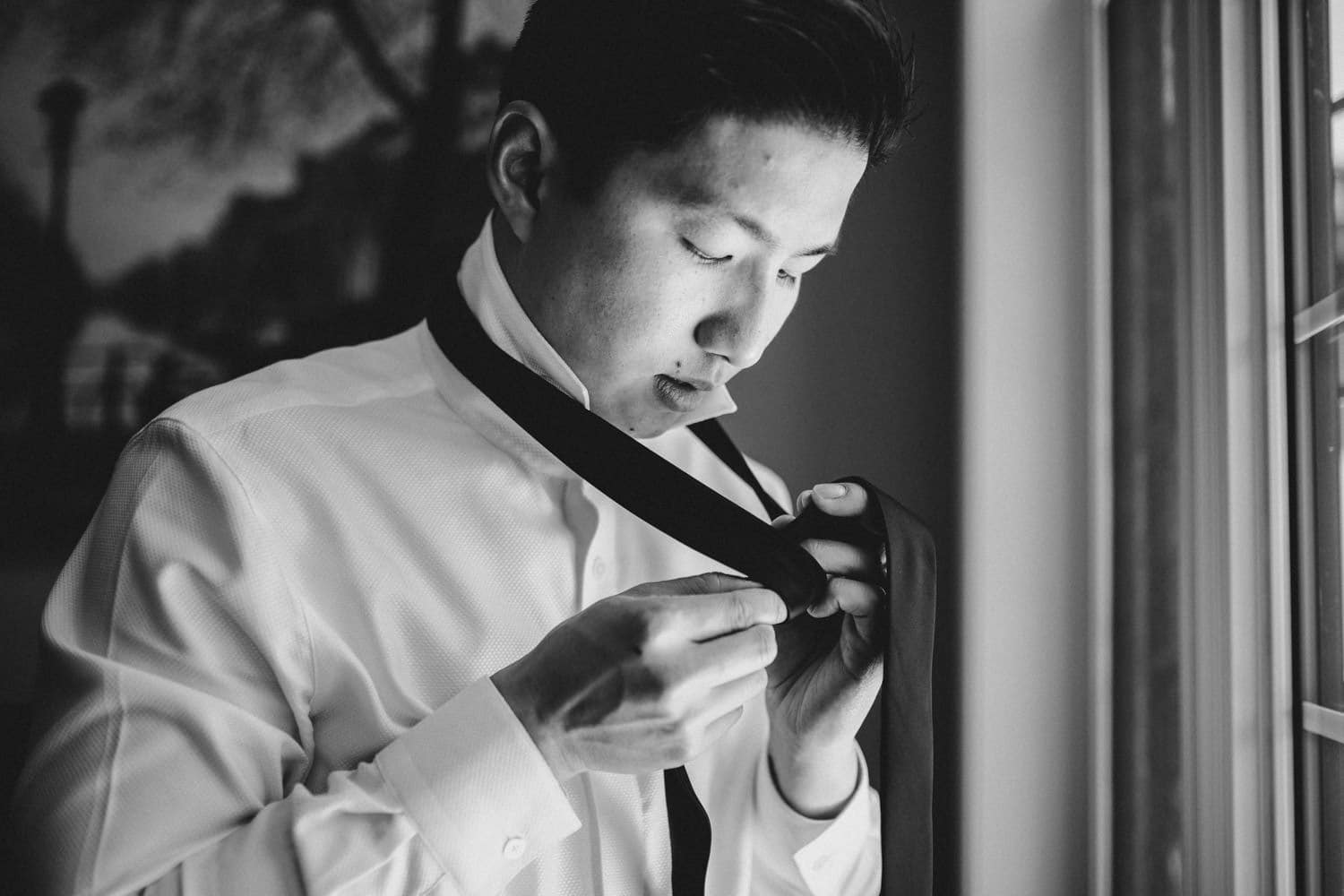 groom getting dressed morning of wedding