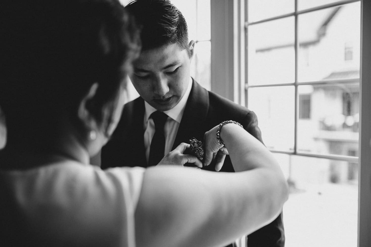 groom's mother helping him with his pocket square