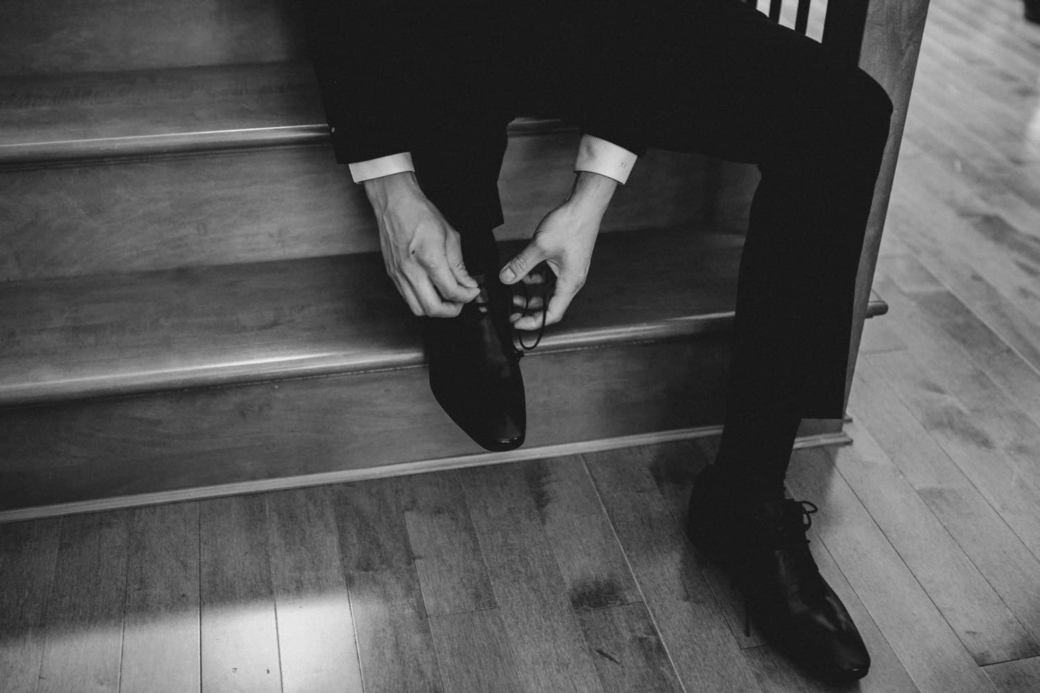 groom tying his shoes morning of wedding