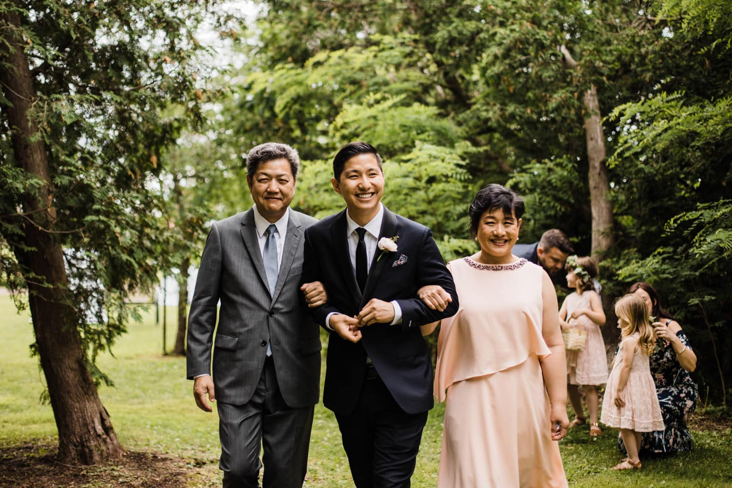 groom walks down the aisle with his parents - backyard wedding ottawa