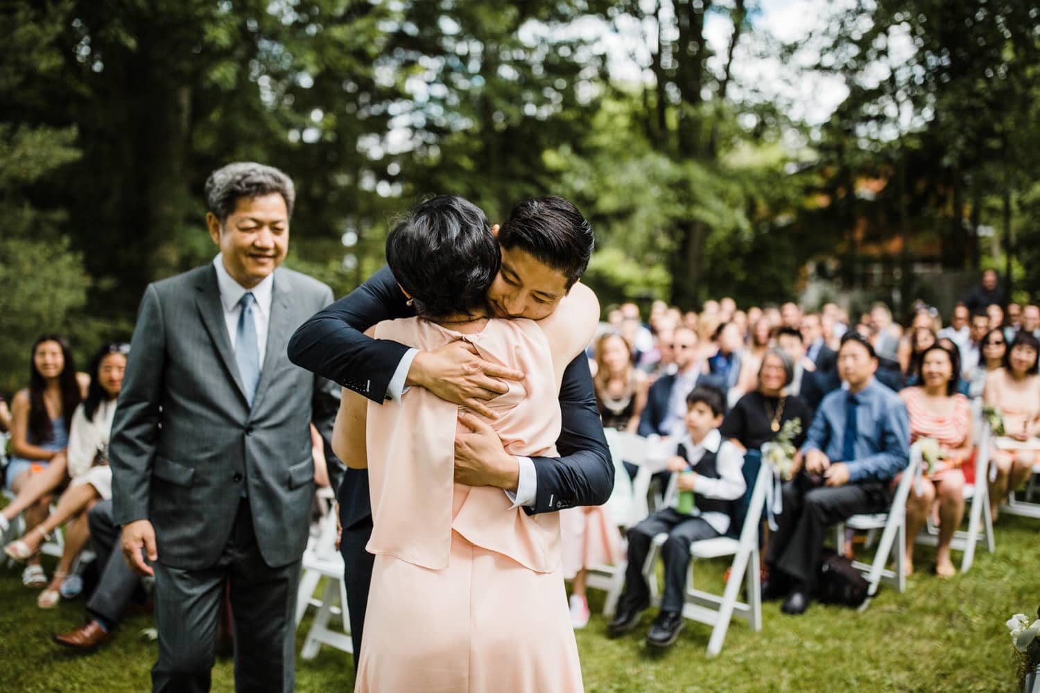 groom hugs his mom during ceremony - ottawa backyard wedding - carley teresa photography