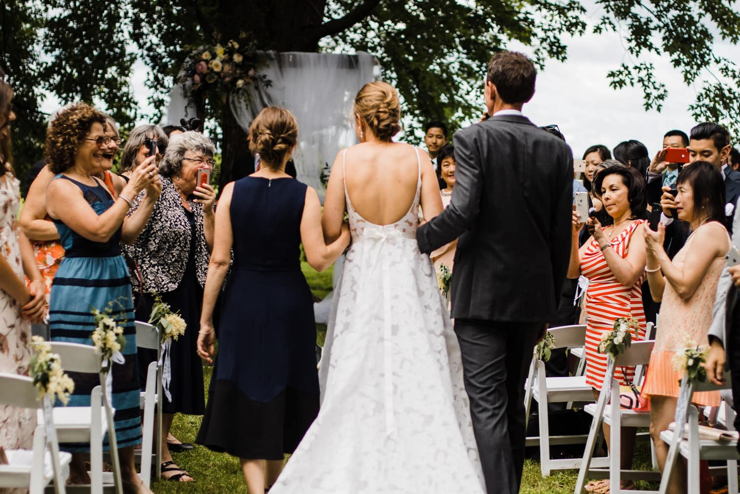 bride walks down the aisle with her parents - ottawa backyard wedding