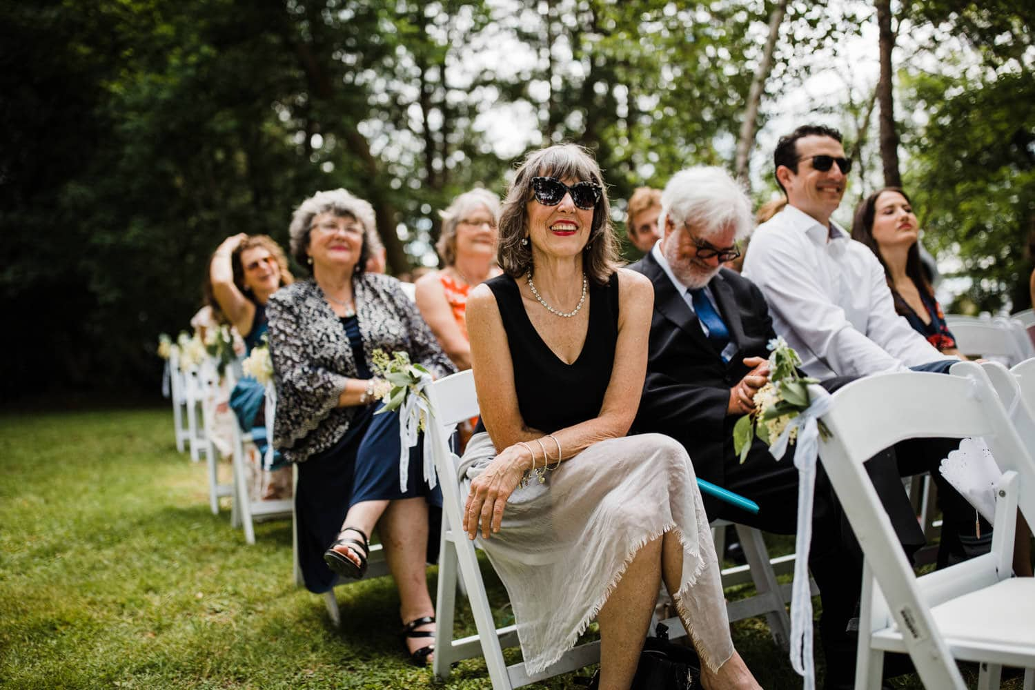 guests laugh during wedding ceremony - ottawa backyard wedding