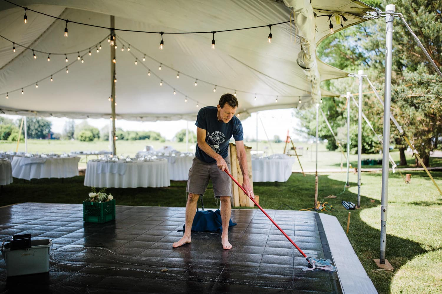 groom's father mops dance floor - backyard wedding ottawa