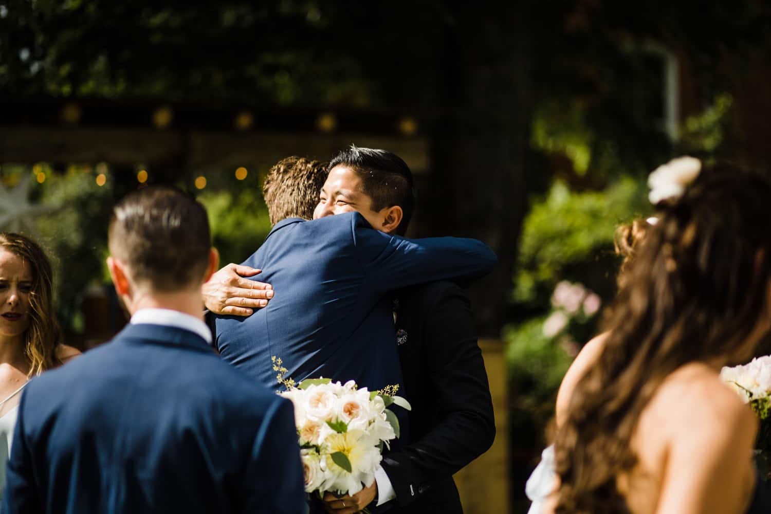 groom hugs his groomsmen after ceremony