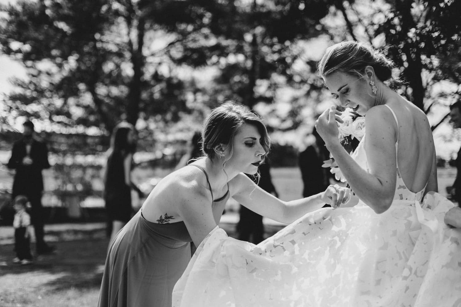 bridesmaid fixes brides dress