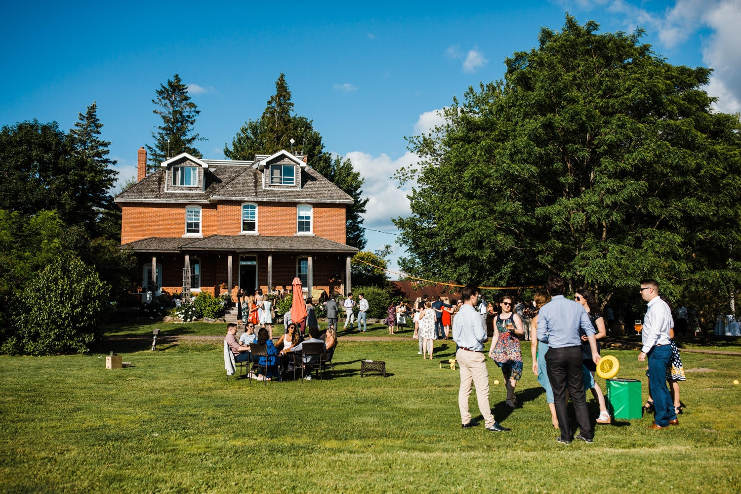 guests mingle and play lawn games - ottawa backyard wedding