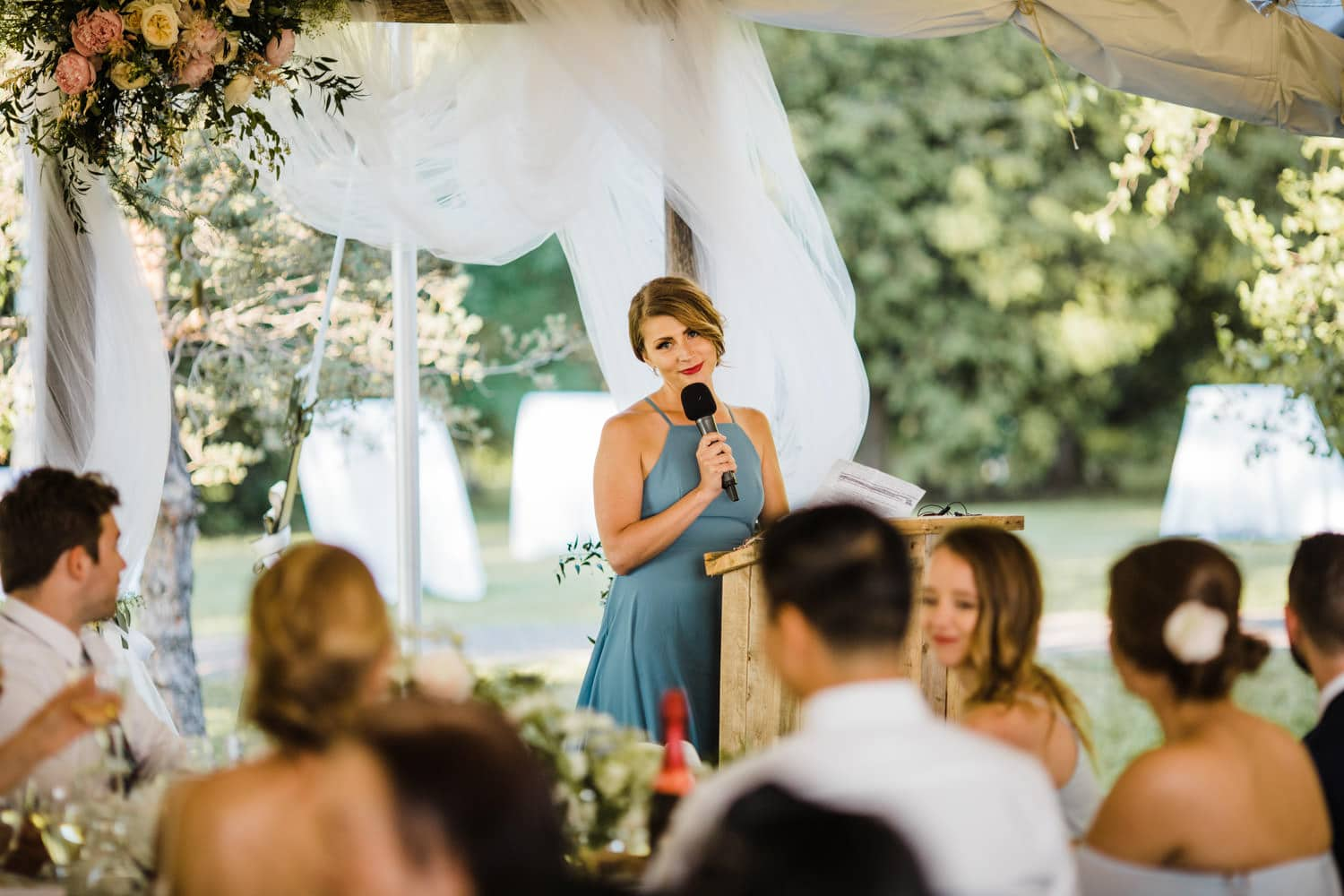 bridesmaid looks lovingly at bride during speech - ottawa backyard wedding - carley teresa photography