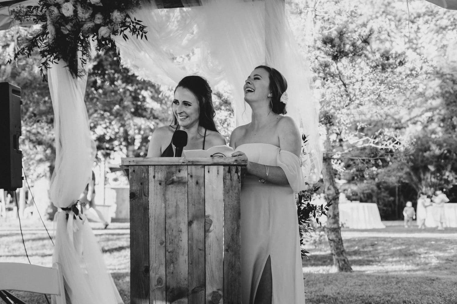 bride's sisters laugh during speech