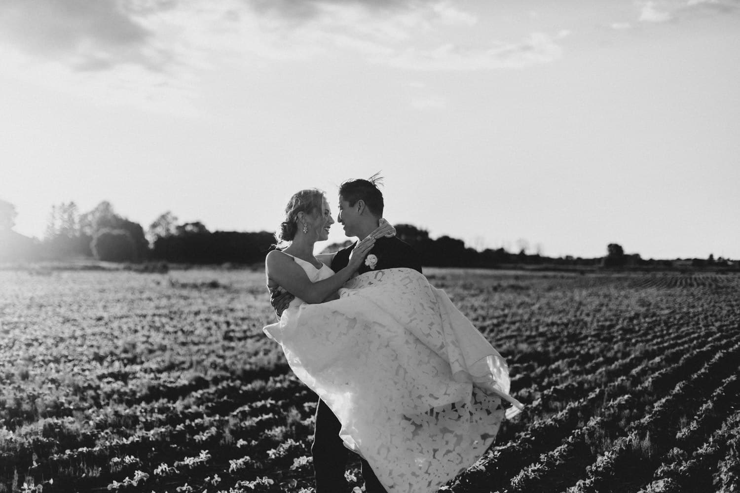 groom picks up bride in a field at sunset - ottawa backyard wedding