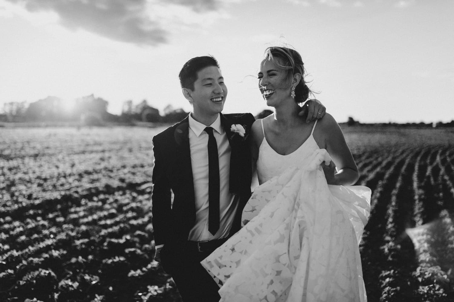 bride and groom laugh together in a field - ottawa backyard wedding