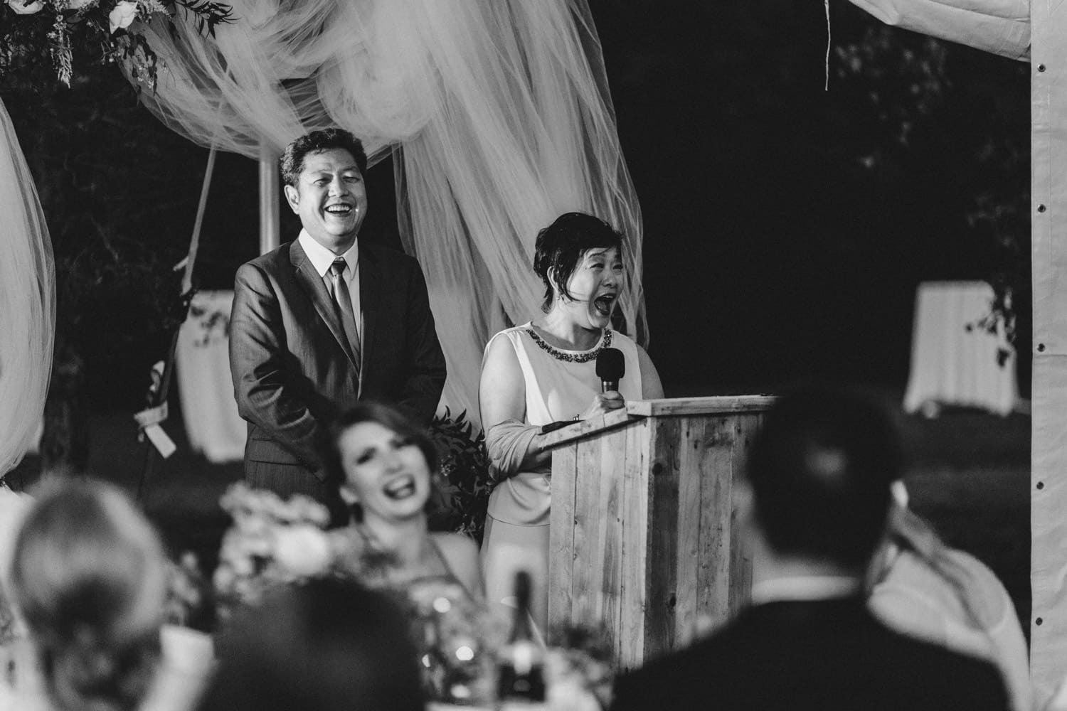 groom's parents give a speech under a tent