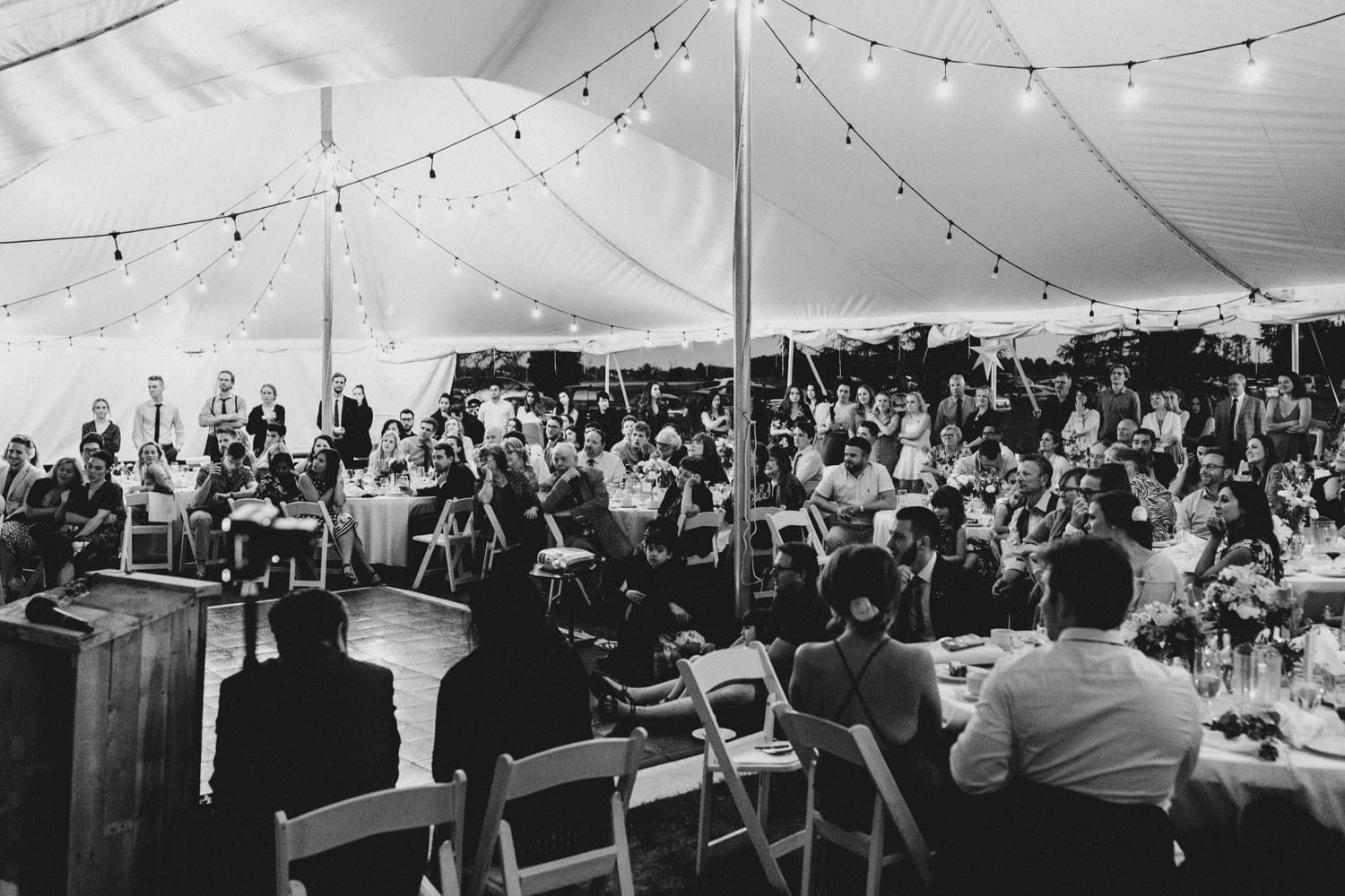 guests listen to speeches under tent - backyard wedding ottawa