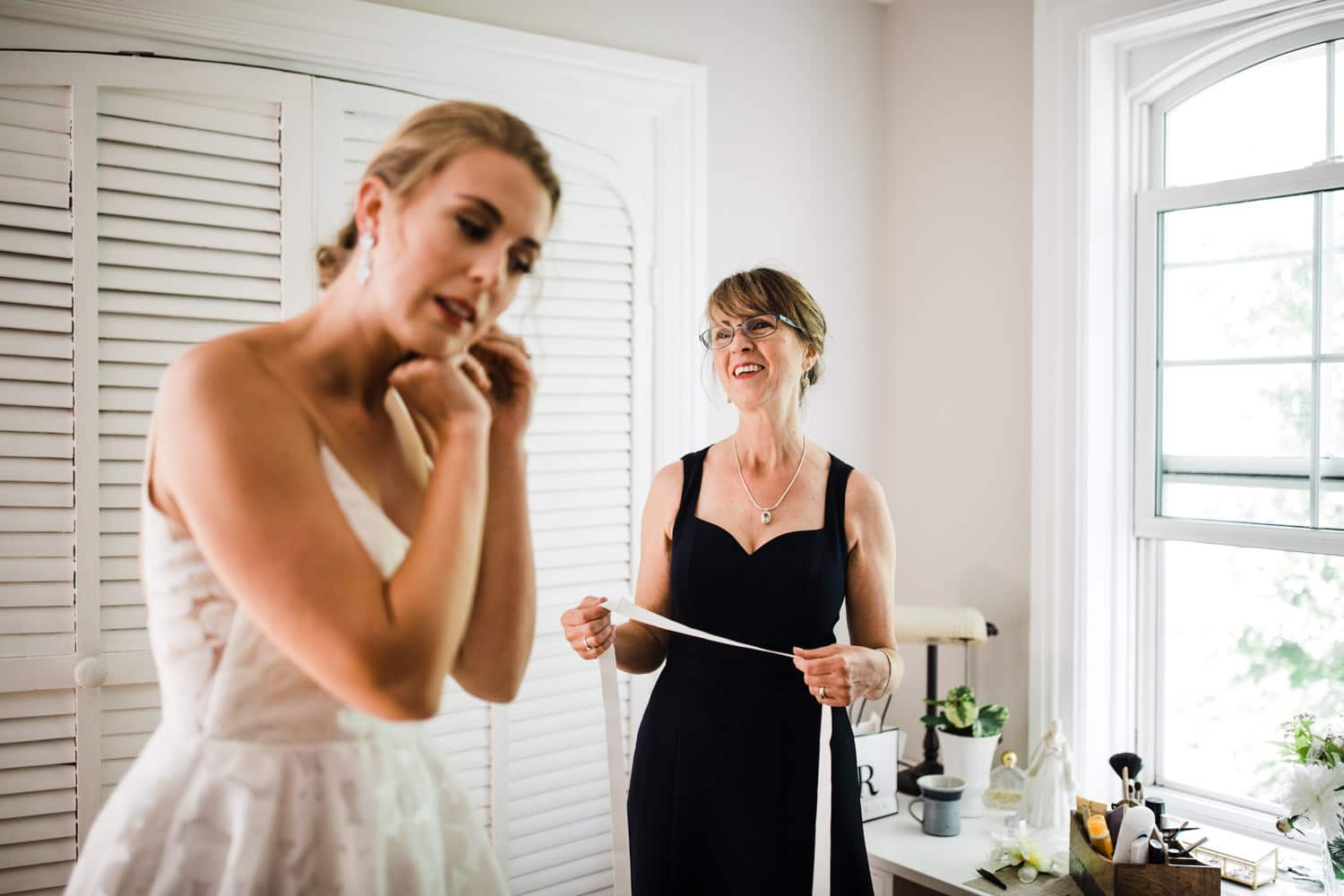 bride's mom helps her get dressed - backyard wedding