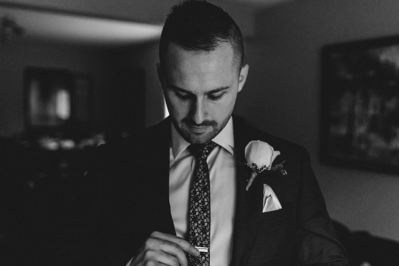 groom adjusts tie clip