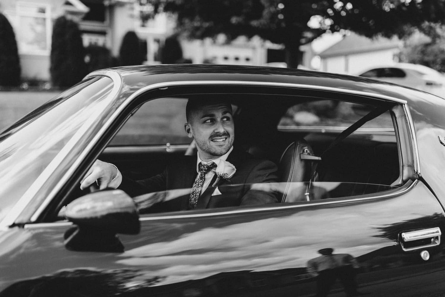 black and white portrait of groom in a vintage car