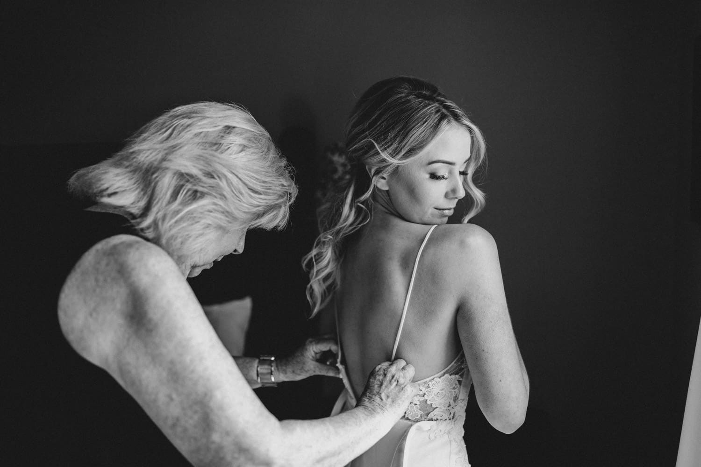 bride's aunt helps her into her dress - summer strathmere wedding
