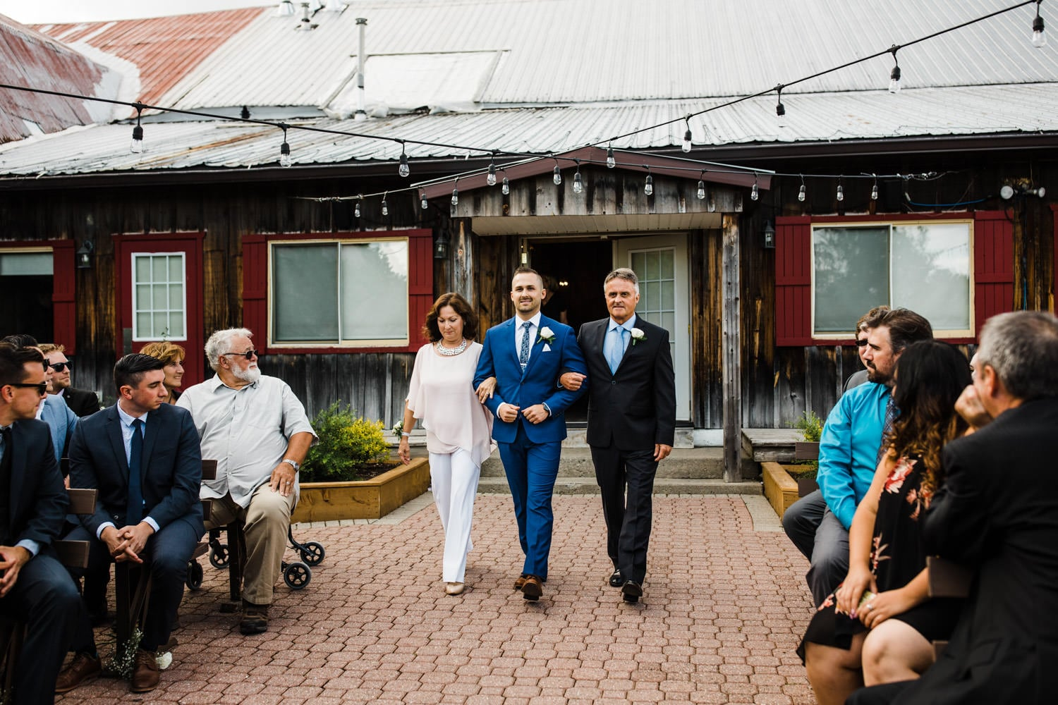 groom walks down aisle with parents - summer strathmere wedding