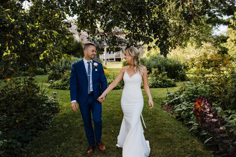 bride and groom walk through garden - summer strathmere wedding