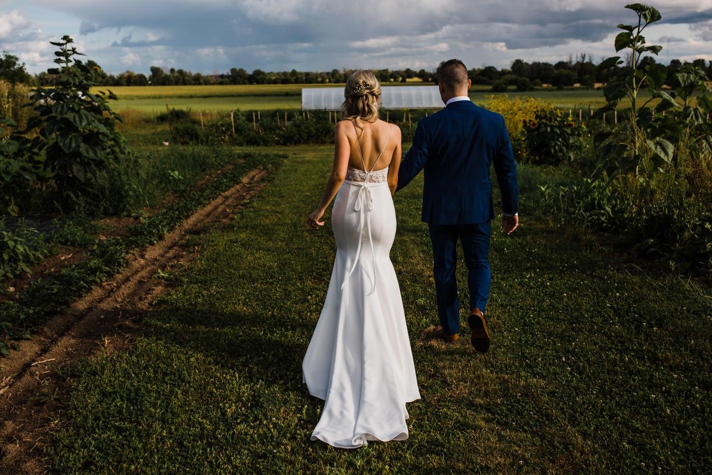 bride and groom walk through garden - carley teresa photography