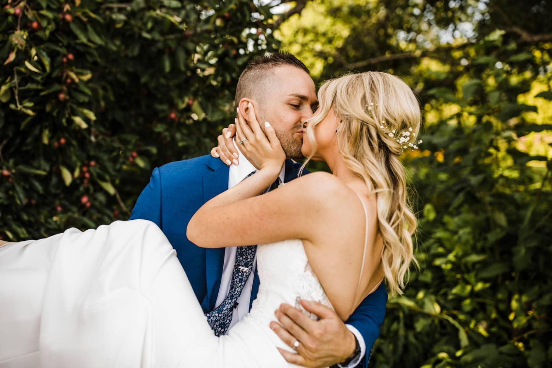 groom picks up bride and kisses her - summer strathmere wedding
