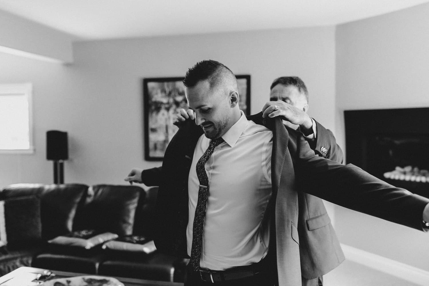groom's dad helps him with jacket