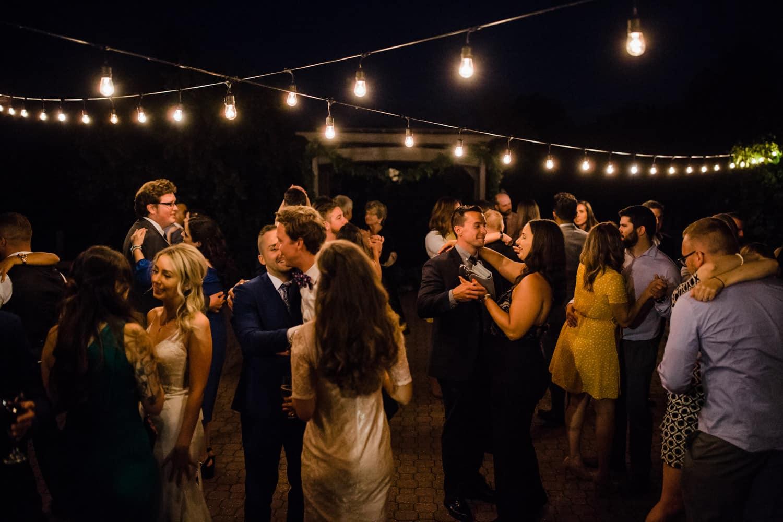 guests dance under string lights - summer strathmere wedding